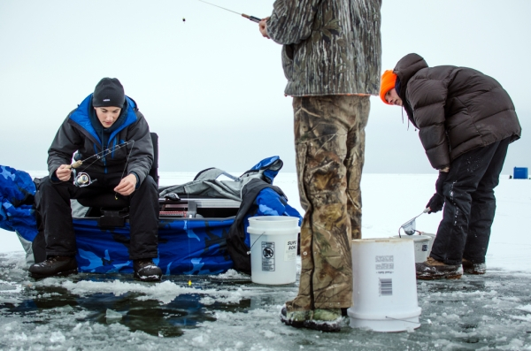 Danielle McGrew | MLive.com Ryan Weiss prepares a line while ice fishing with his buddies Jonny Engelhardt and Rylan Appold on the Saginaw Bay in Linwood on Friday, Nov. 29. The group said it was the first time they were able to go ice fishing this season.