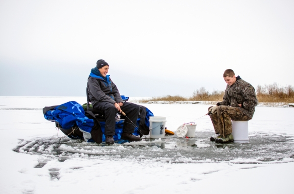 Danielle McGrew | MLive.com Ryan Weiss and Jonny Engelhardt joke as they fish for perch on the frozen Saginaw Bay in Linwood on Friday, Nov. 29. The group said it was the first time they were able to go ice fishing this season.