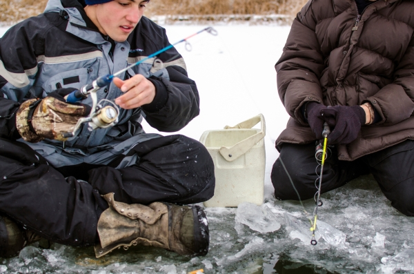 Danielle McGrew | MLive.com Josh Appold checks his line while fishing with Rylan Appold on the frozen Saginaw Bay in Linwood on Friday, Nov. 29.The group said it was the first time they were able to go ice fishing this season.
